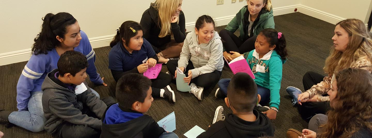 Young students sit together and share stories.