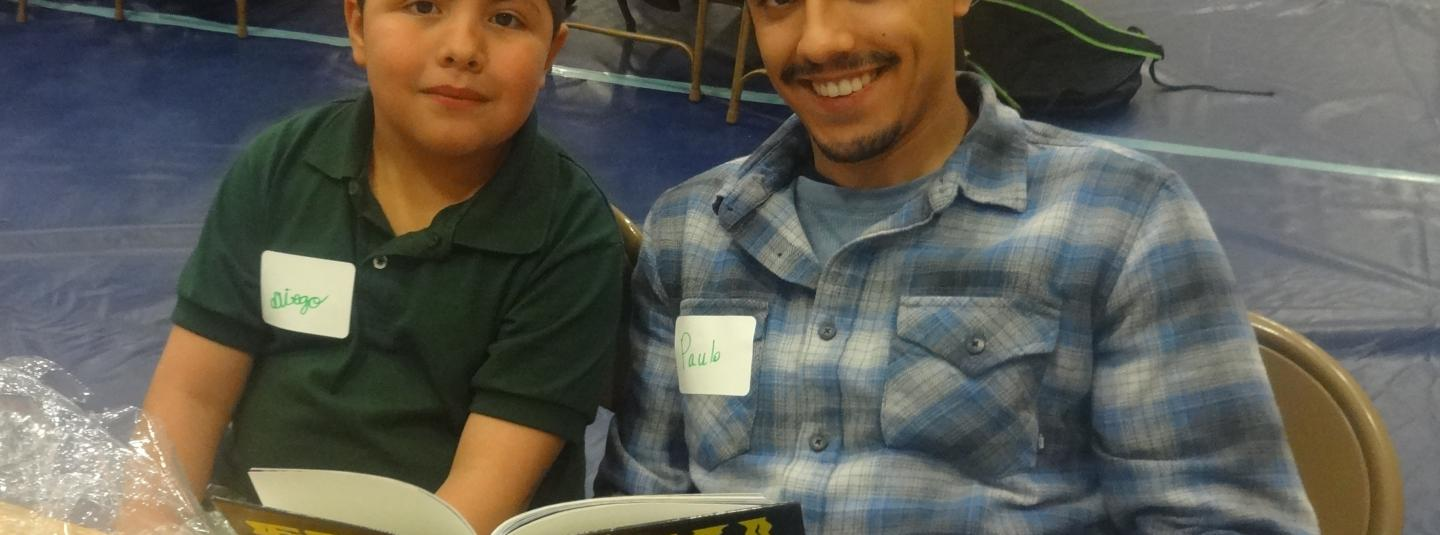 Luther Burbank student, Diego, and their SSU student partner, Paulo, reading a book together.