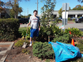 A Student standing with a shovel in a garden