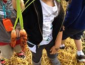 A child holding up carrots to the camera